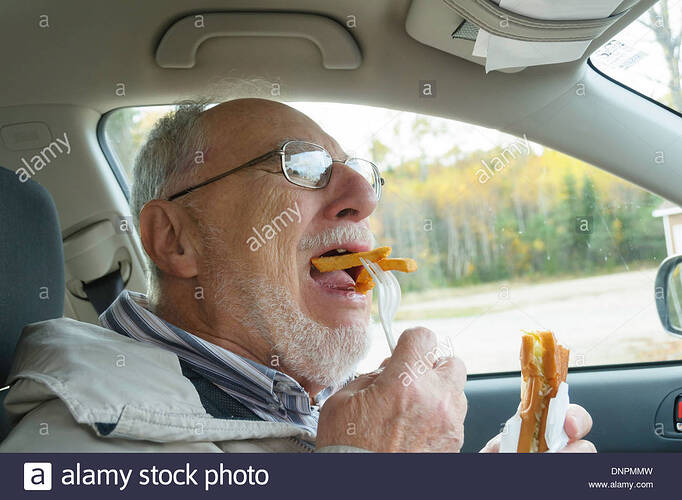 senior-man-with-expressive-face-eating-fast-foods-in-his-car-french-DNPMMW